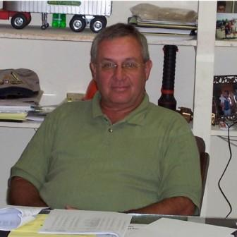 Photograph of Bobby Berkstresser seated in his office with model trucks, caps and snapshots behind him.
